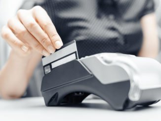Bank terminal and a woman's hand with a credit or debit card to make payments.